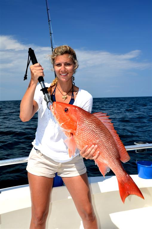 girl-holding-red-snapper-on-distraction-charter-boat