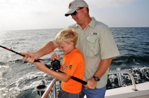 dad helping son reel in a fish