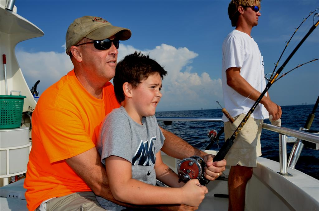 reeling in a big fish while trolling fishing near shore