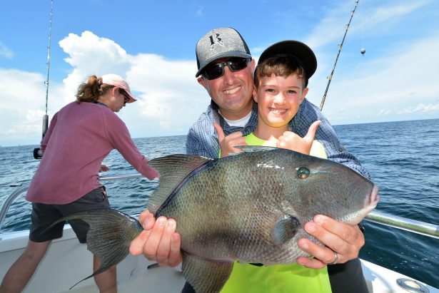 Father son holding triggerfish