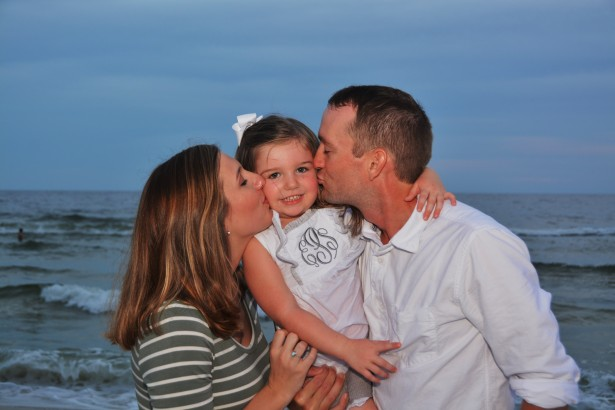 mom-dad-kissing-daughter-on-beach
