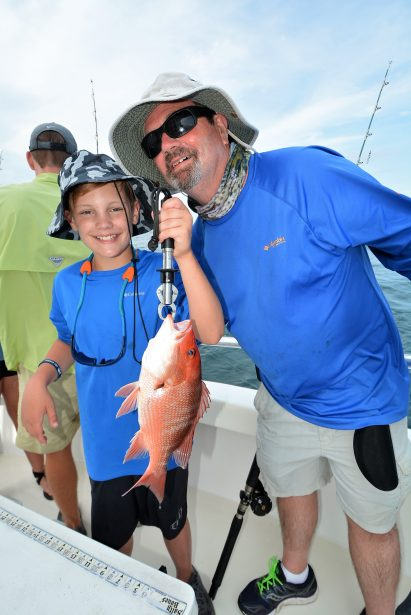 grandpa-grandson-fishing-holding-red-snapper