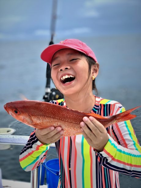 Girl holding vermilion snapper fish